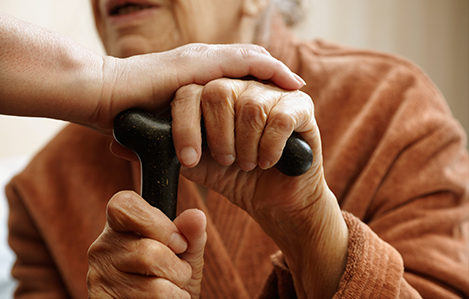 Photo of an elderly person's hands on a cane